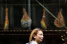 España redujo un 29 por ciento su déficit comercial en los nueve primeros meses del año, hasta los 13.227,1 millones de euros, dijo el lunes el Ministerio de Economía, registrando el segundo mejor saldo desde 1997. En esta imagen de archivo, una mujer pasa junto a una tienda de jamones en San Petersburgo el 13 de agosto de 2014.  REUTERS/Alexander Demianchuk (