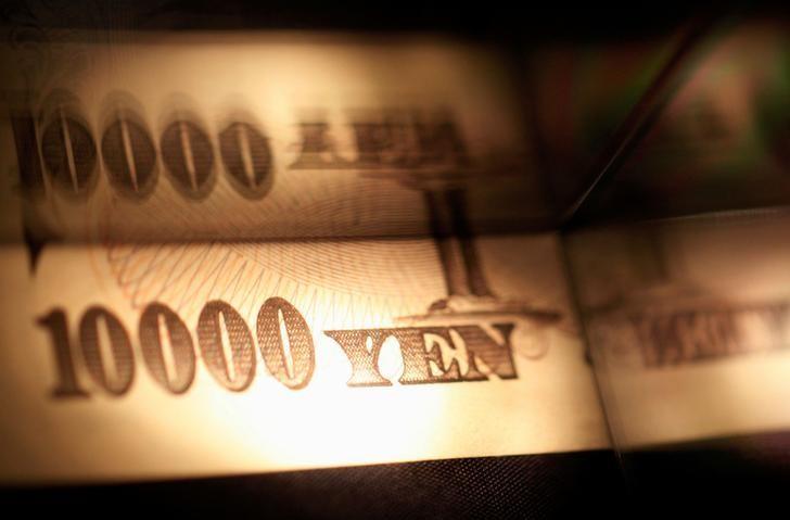 2013年2月28日,图中一束光落在一张日元纸币上。REUTERS/Shohei Miyano