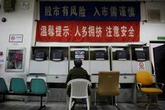 """Инвестор смотрит на экран с информацией о торгах в брокерской компании Шанхая. Ведущий фондовый индекс Китая установил в пятницу новый рекорд роста, завершив лучшую за примерно полгода неделю, в течение которой инвесторы скупали """"голубые фишки"""" ввиду признаков стабилизации экономики.   REUTERS/Aly Song"""