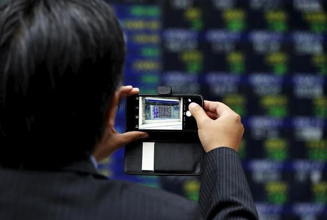 11月28日、前場の東京株式市場で、日経平均株価は前営業日比146円32銭安の1万8234円90銭と8日ぶりに反落した。前週末の米国株は上昇したものの、強含みの円相場を嫌気して朝方から輸出株中心に売りが先行した。写真は都内の株価ボード。昨年6月撮影(2016年 ロイター/Issei Kato)