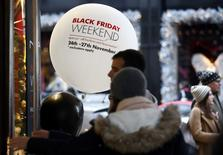 """Las promociones adelantadas y la confianza en que las gangas seguirán disponibles redujeron el gasto de los consumidores en el fin de semana de Acción de Gracias, que en Estados Unidos da inicio a la temporada de compras navideñas. En  la imagen, compradores junto a la entrada de una tienda que promocioona el """"Black Friday"""" en Londres, el 27 de noviembre de 2016.  REUTERS/Peter Nicholls"""