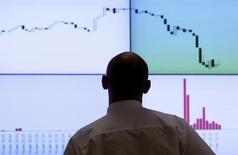 Трейдер смотрит на график индекса РТС. Российские фондовые индексы слегка снизились в понедельник на фоне отката цен на нефть и после успеха предыдущей недели.  REUTERS/Denis Sinyakov  (RUSSIA - Tags: BUSINESS)