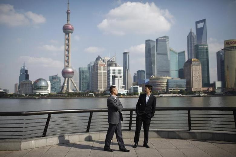 2011年11月21日,上海,两名男子在与浦东金融区隔江相望的外滩交谈。REUTERS/Aly Song