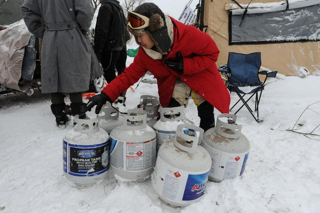 A woman gathers empty propane canisters in the Oceti Sakowin camp during a protest against plans to pass the Dakota Access pipeline near the Standing Rock Indian Reservation, near Cannon Ball, North Dakota, U.S. November 30, 2016. REUTERS/Stephanie Keith