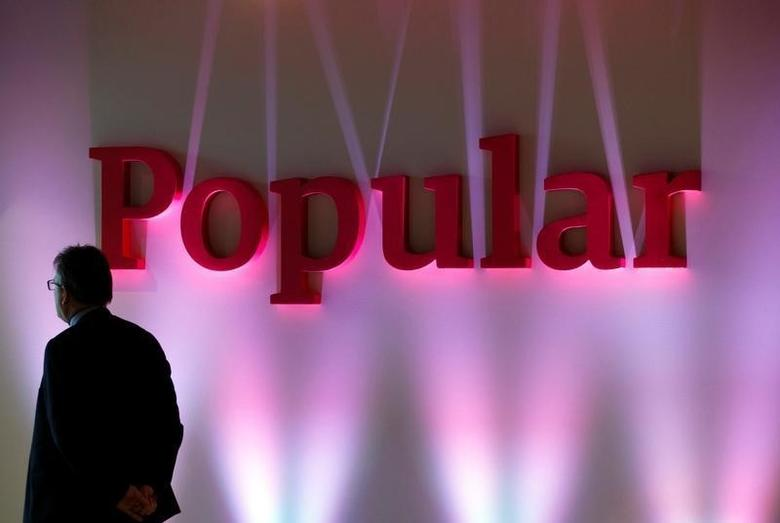 A man stands next to the logo of Spain's Banco Popular during the bank's results presentation in Madrid January 30, 2015. REUTERS/Sergio Perez/File Photo