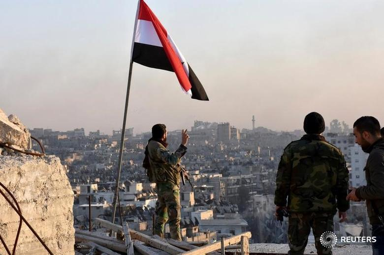 A Syrian government soldier gestures a v-sign under the Syrian national flag near a general view of eastern Aleppo after they took control of al-Sakhour neigbourhood in Aleppo, Syria in this handout picture provided by SANA on November 28, 2016. SANA/Handout via REUTERS ATTENTION EDITORS - THIS IMAGE WAS PROVIDED BY A THIRD PARTY. EDITORIAL USE ONLY. REUTERS IS UNABLE TO INDEPENDENTLY VERIFY THIS IMAGE.     TPX IMAGES OF THE DAY - RTSTXPW