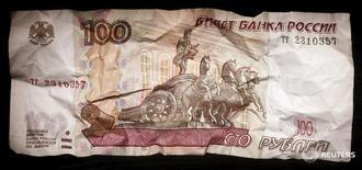 Сторублевая банкнота. Рубль начал снижением торги пятницы на фоне коррекции котировок нефти Brent с 16-месячных максимумов при низкой активности участников рынка перед публикацией трудовой статистики США, которая будет влиять на решение ФРС по ставкам на заседании 13-14 декабря. REUTERS/Maxim Zmeyev