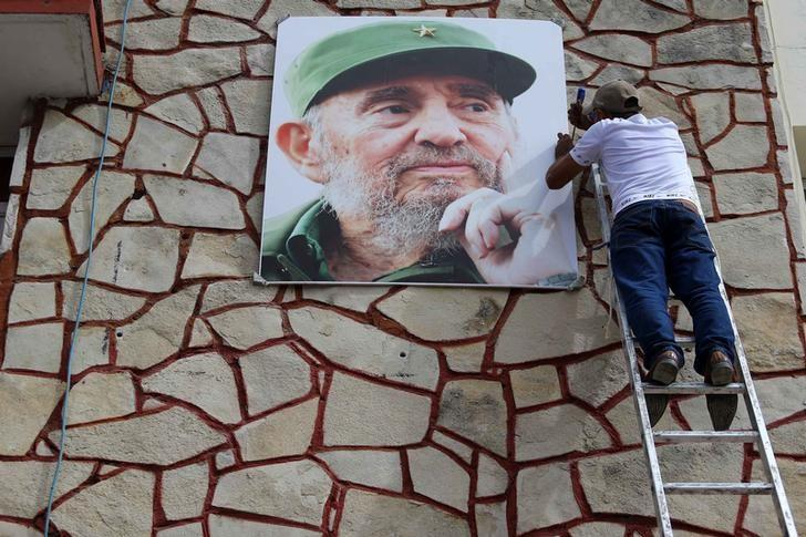 A man works on a portrait of Cuba's late President Fidel Castro as the town prepares for the arrival of the caravan carrying Castro's ashes in Las Tunas, Cuba, December 1, 2016. REUTERS/Ivan Alvarado
