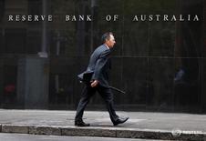 Мужчина проходит мимо здания Резервного банка Австралии в Сиднее 4 февраля 2014 года. Австралийский центробанк во вторник оставил ставки без изменений по итогам последнего в этом году заседания, но предупредил о рисках, виной чему череда слабых данных, указавших на возможное замедление экономики страны в третьем квартале. REUTERS/Jason Reed/File Photo
