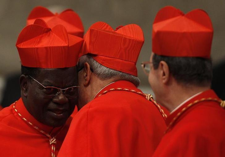 New cardinal Laurent Monsengwo Pasinya of Democratic Republic of Congo (L) is congratulated by other cardinals after receiving the red biretta, a four-cornered red hat, from Pope Benedict XVI during the Consistory ceremony in Saint Peter's Basilica at the Vatican November 20, 2010.  Pope Benedict installed 24 new Roman Catholic cardinals from around the world on Saturday in his latest batch of appointments that could include his successor as leader of the 1.2 billion member church. REUTERS/Tony Gentile   (VATICAN - Tags: RELIGION)