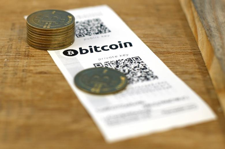 A Bitcoin paper wallet with QR codes and coins are seen in an illustration picture.  REUTERS/Benoit Tessier