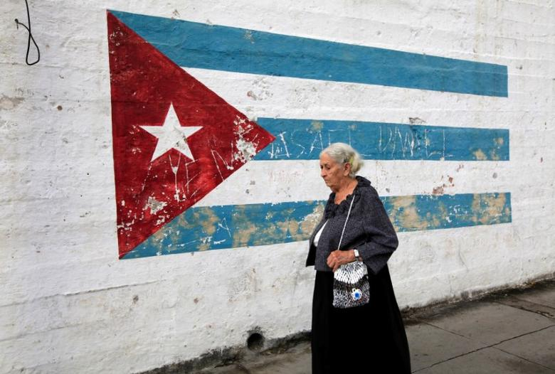 An old woman walks in front of a mural of the Cuban flag in Havana, Cuba November 27, 2016. REUTERS/Enrique de la Osa