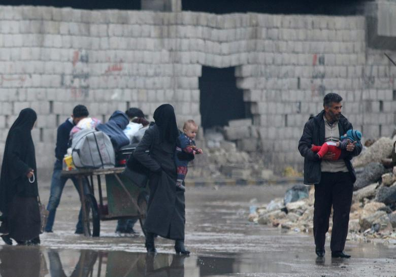 Civilians carry their belongings as they flee deeper into the remaining rebel-held areas of Aleppo, Syria December 7, 2016. REUTERS/Abdalrhman Ismail