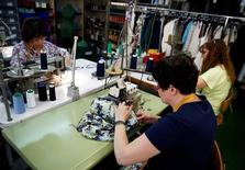 Los costes laborales en España recuperaron el ritmo de principios de año tras el bajón del verano y subieron en el tercer trimestre un 0,7 por ciento interanual en datos desestacionalizados, dijo el viernes el Instituto Nacional de Estadística (INE). En la imagen, trabajadoras en una fábrica textil en Madrid, 19 de mayo de 2014. REUTERS/Andrea Comas