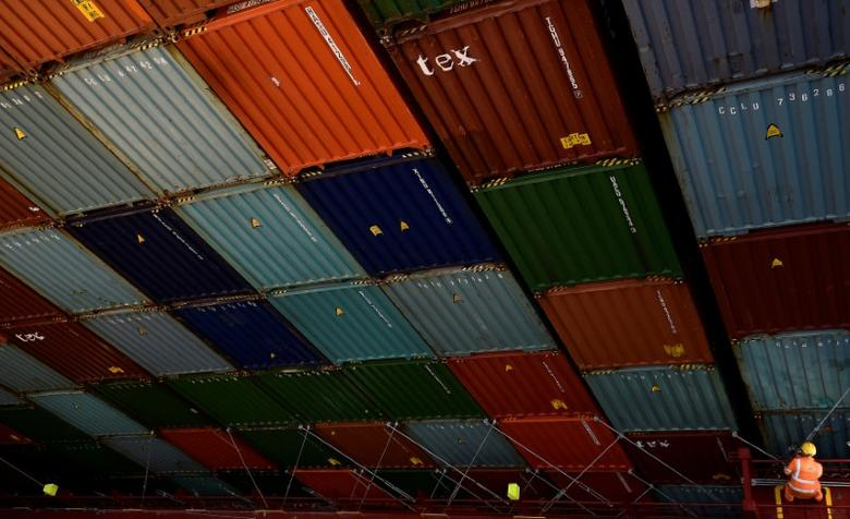 A port worker releases containers for unloading at the port of Felixstowe, Britain, January 7, 2015. REUTERS/Toby Melville/File Photo