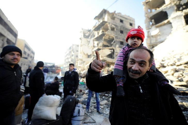 People, who evacuated the eastern districts of Aleppo, stand with their belongings in a government held area of Aleppo, Syria December 9, 2016. REUTERS/Omar Sanadiki
