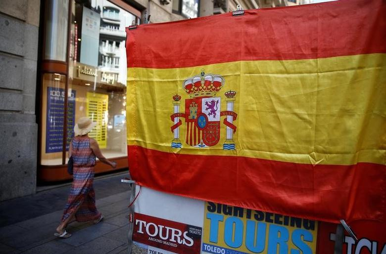 A woman walks past a Spanish flag in central Madrid, Spain, August 24, 2016. Picture taken August 24, 2016. REUTERS/Andrea Comas