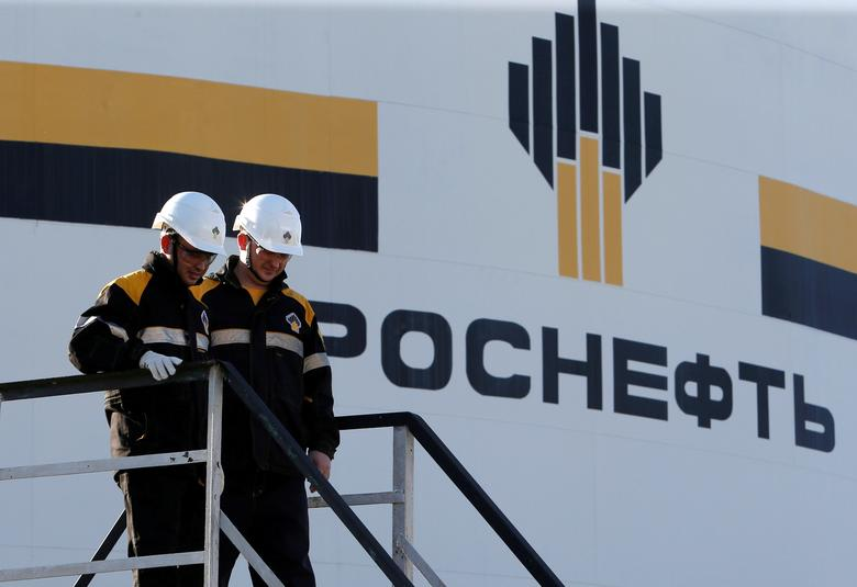 Workers stand next to a logo of Russia's Rosneft oil company at the central processing facility of the Rosneft-owned Priobskoye oil field outside the West Siberian city of Nefteyugansk, Russia, August 4, 2016. REUTERS/Sergei Karpukhin/File Photo