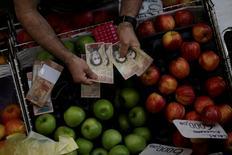 A cashier counts Venezuelan bolivar notes at a market in downtown Caracas, Venezuela, December 7, 2016. REUTERS/Ueslei Marcelino