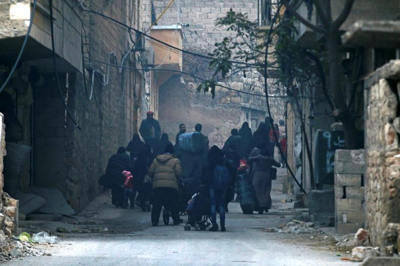 People carry belongings as they flee deeper into the remaining rebel-held areas of Aleppo, Syria December 12, 2016. REUTERS/Abdalrhman Ismail