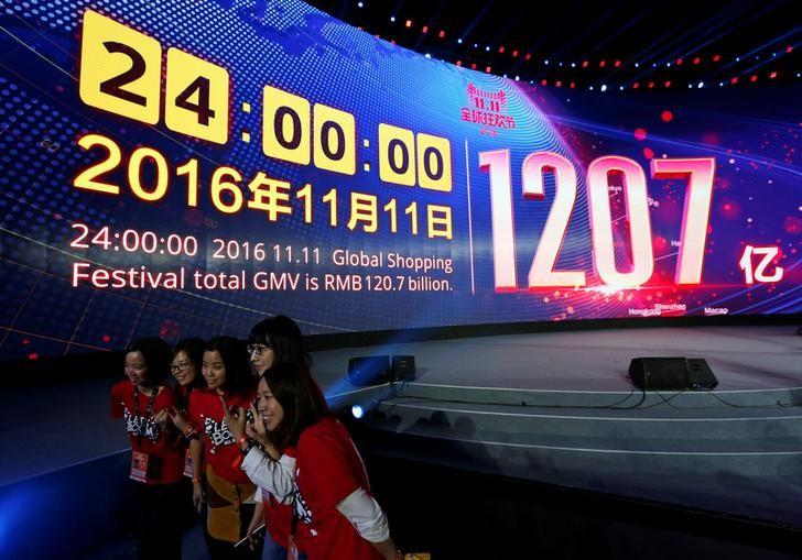 Attendants celebrate in front of a screen displaying the total value of goods sold during Alibaba Group's 11.11 Singles' Day global shopping festival in Shenzhen, China, November 12, 2016. REUTERS/Bobby Yip/Files