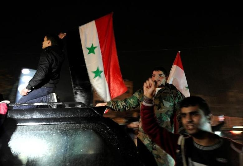 Supporters of Syria's President Bashar al-Assad carry their national flags as they celebrate what they say is the Syrian army's victory against the rebels, in Aleppo, Syria December 12, 2016. REUTERS/Omar Sanadiki
