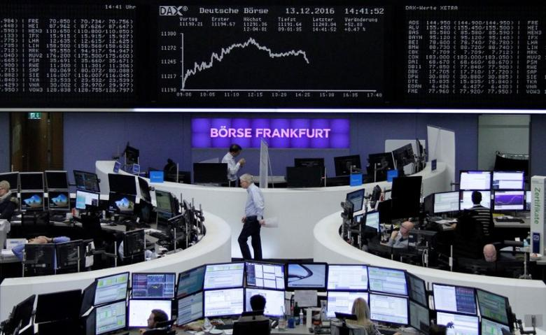 Traders work at their desks in front of the German share price index, DAX board, at the Stock Exchange in Frankfurt, Germany December 13, 2016. REUTERS/Staff/Remote