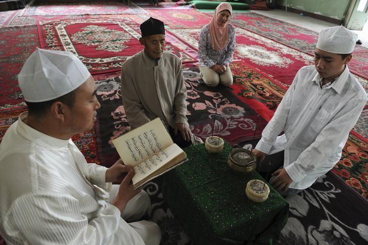 A Muslim man from the Chinese Hui minority reads the Koran as others listen in a sitting room in Aksu, Xinjiang Uighur Autonomous Region July 27, 2012. Picture taken July 27, 2012.  REUTERS/Stringer
