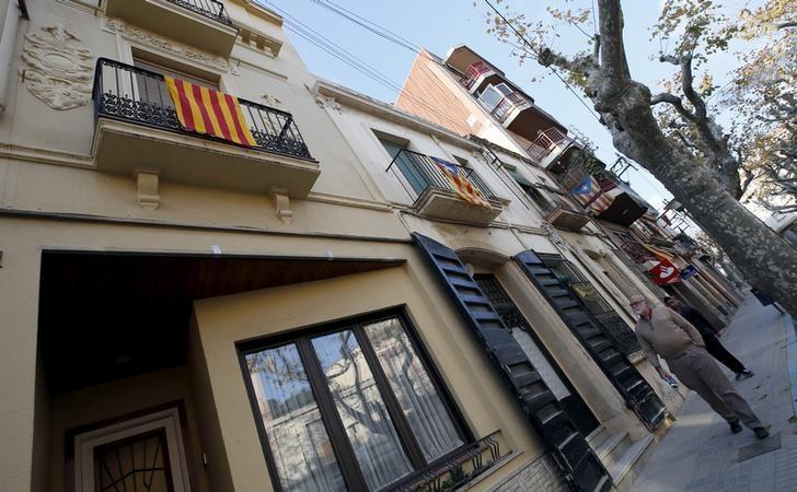 A man looks at ''Esteladas'' (Catalan separatist flags) hanging from a balcony as he walks by Arenys de Munt town, near Barcelona, Spain, December 9, 2015. REUTERS/Albert Gea