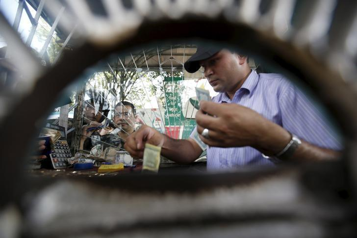 A man works inside the cash counter of a petrol station as people gather around to fill petrol for their vehicle in Kathmandu, Nepal September 28, 2015.  REUTERS/Navesh Chitrakar/Files