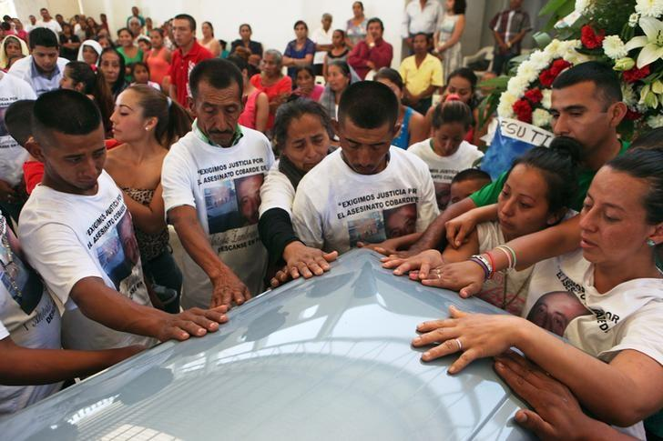 Relatives and friends of Antonio Zambrano-Montes touch his coffin during a funeral mass in Pomaro, in the Mexican state of Michoacan March 7, 2015. REUTERS/Alan Ortega/Files