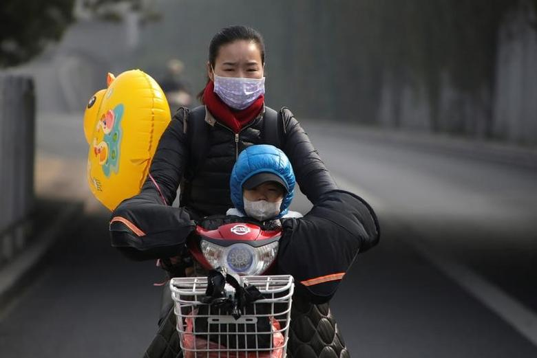 A woman and her son wearing masks ride an electric bicycle on a hazy day in Beijing, China, November 4, 2016. REUTERS/Jason Lee/Files