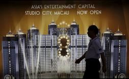 A man walks past an advertisement of Macau's Studio City resort, owned by Melco Crown Entertainment, in Hong Kong, China November 10, 2015.      REUTERS/Bobby Yip/File Photo