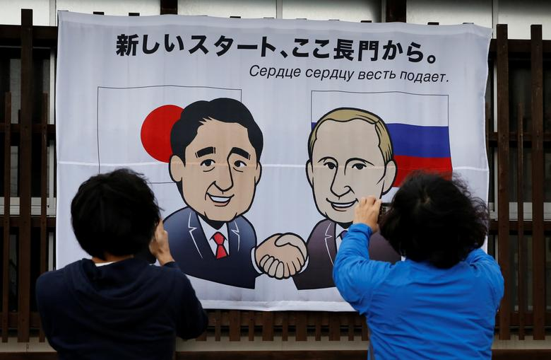 People take photos of a banner showing Japan's Prime Minister Shinzo Abe and Russian President Vladimir Putin at the Senzaki station in Nagato, Yamaguchi prefecture, Japan, December 14, 2016, a day before their summit meeting. The words on top reads, ''A new start from here in Nagato''.    REUTERS/Toru Hanai