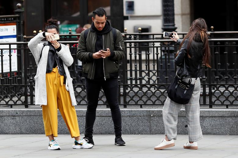 People look at their mobile phones at Piccadilly Circus in London, Britain October 6, 2016. REUTERS/Stefan Wermuth
