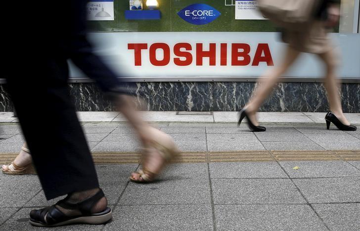 Pedestrians walk past a logo of Toshiba Corp outside an electronics retailer in Tokyo September 14, 2015.   REUTERS/Toru Hanai/File Photo