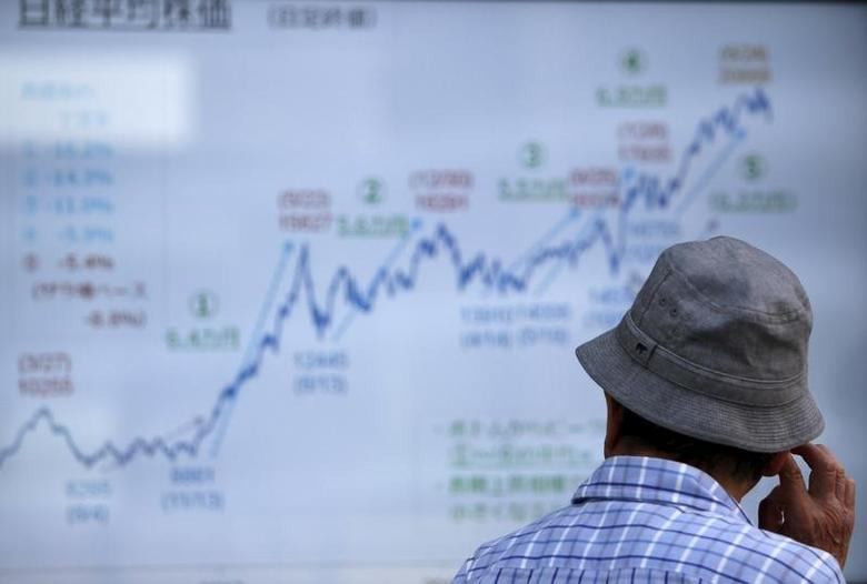 A man looks at an electronic graph showing recent movement of Japan's Nikke share average outside a brokerage in Tokyo July 13, 2015.   REUTERS/Issei Kato