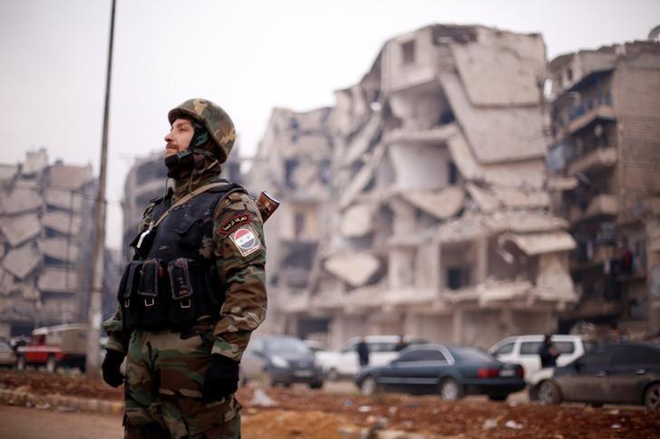 A member of forces loyal to Syria's President Bashar al-Assad stands near damaged buildings in Aleppo's Salaheddine district, Syria December 16, 2016. REUTERS/Omar Sanadiki