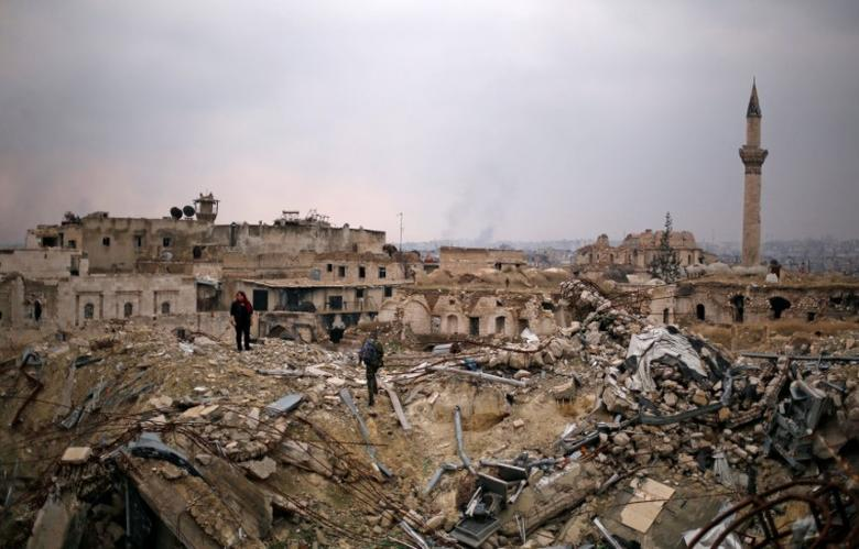 A member of forces loyal to Syria's President Bashar al-Assad stands with a civilian on the rubble of the Carlton Hotel, in the government controlled area of Aleppo, Syria December 17, 2016. REUTERS/Omar Sanadiki