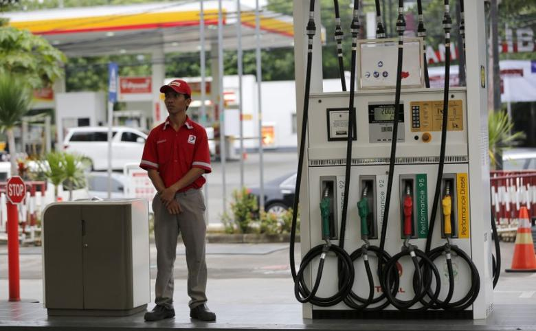 An employee at a Total fuel station waits for customers in south Jakarta February 12, 2015. REUTERS/Darren Whiteside