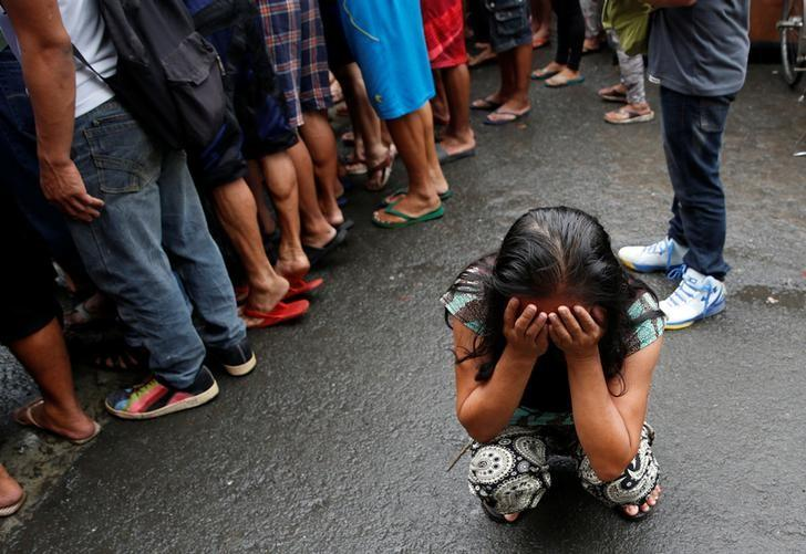 A family friend weeps after Nora Acielo, 47, was gunned down by unidentified men while escorting her two children to school in Manila, Philippines December 8, 2016. Police said Acielo was among more than 30 people slain over the last three days in drugs related killings. REUTERS/Erik De Castro