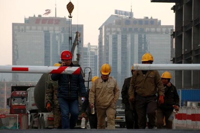 Workers leave a construction site at the end of their shift in Beijing, China December 6, 2016. REUTERS/Thomas Peter