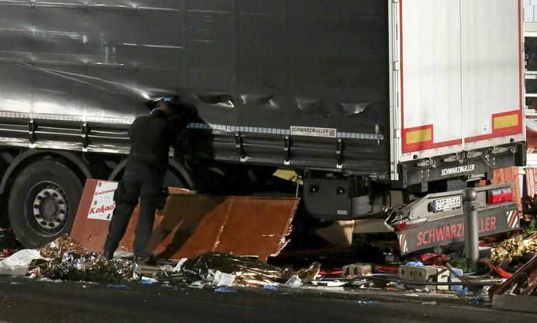A German police officer looks into a truck at a Berlin Christmas market following an accident with the truck on Breitscheidplatz square near the fashionable Kurfuerstendamm avenue in the west of Berlin, Germany, December 19, 2016.    REUTERS/Christian Mang