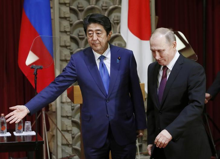 Japanese Prime Minister Shinzo Abe shows the way to Russian President Vladimir Putin during a joint news conference in Tokyo, Japan, December 16, 2016. REUTERS/Alexander Zemlianichenko/Pool