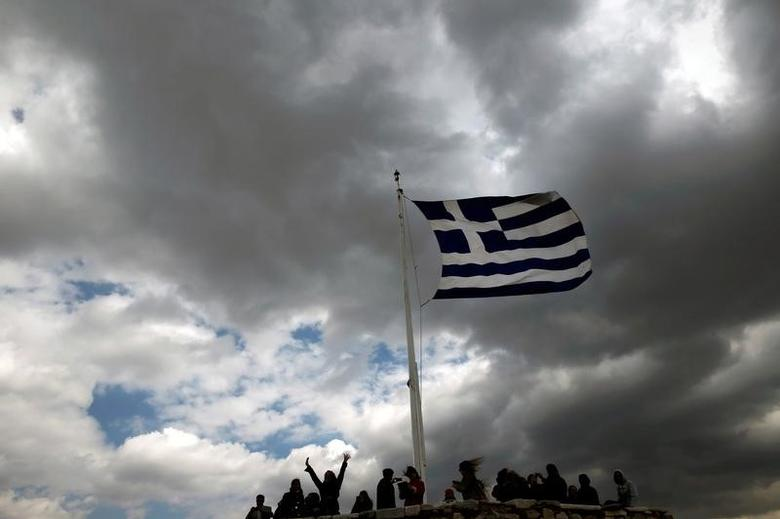 People are silhouetted under a fluttering Greek national flag atop the archaeological site of the Athens Acropolis, Greece, March 20, 2015.  REUTERS/Alkis Konstantinidis/File Photo