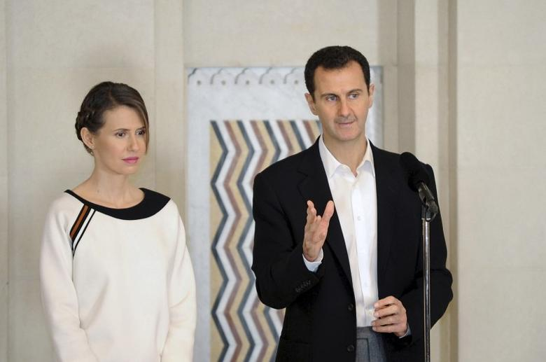 Syria's President Bashar al-Assad stands next to his wife Asma, as he addresses injured soldiers and their mothers during a celebration marking Syrian Mother's Day in Damascus, in this handout picture provided by SANA on March 21, 2016. SANA/Handout via REUTERS