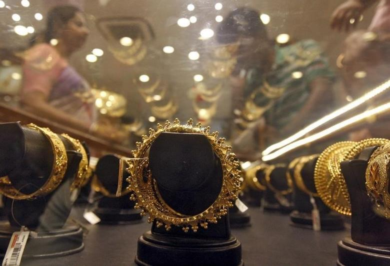 Gold bracelets are on display as a woman (L) makes choices at a jewellery showroom on the occasion of Akshaya Tritiya, a major gold buying festival, in Kolkata April 21, 2015.  REUTERS/Rupak De Chowdhuri