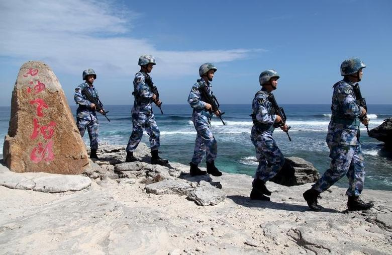 Soldiers of China's People's Liberation Army (PLA) Navy patrol at Woody Island, in the Paracel Archipelago, which is known in China as the Xisha Islands, January 29, 2016. The words on the rock read, ''Xisha Old Dragon''. Old Dragon is the local name of a pile of rocks near Woody Island. REUTERS/Stringer/Files
