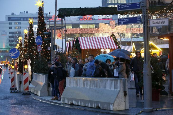 People leave the re-opened Christmas market at Breitscheid square in Berlin, Germany, December 22, 2016, following an attack by a truck which ploughed through a crowd at the market on Monday night.      REUTERS/Fabrizio Bensch
