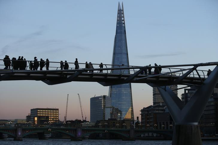 The Shard building catches the early evening light as tourists cross the Millennium Bridge in London, Britain December 4, 2016.  REUTERS/Peter Nicholls